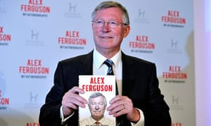 Alex Ferguson holding up his book