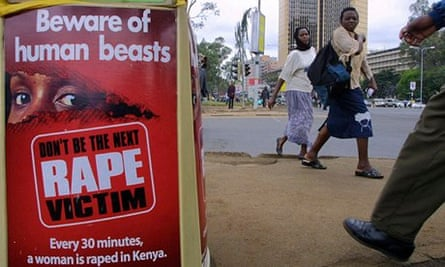 People walk past a poster bearing a message against rape on a street of Nairobi, Kenya.