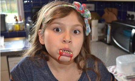 Fake blood: child with fake vampire fangs and blood