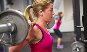 Blond women in pink top doing back squats with barbell in weight gym.