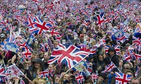 Flag-waving crowds gather to watch the Queen's diamond jubilee procession in London last year.