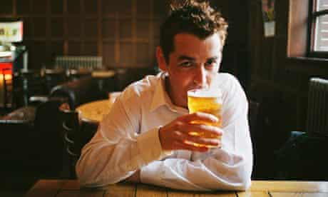 Man drinking pint of beer in pub