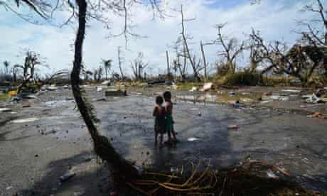 Two young boys look at the devastation in the aftermath of typhoon Haiyan