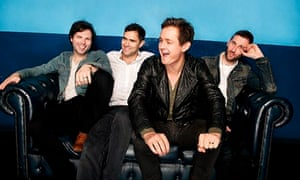The four band members laugh heartily on a leather sofa