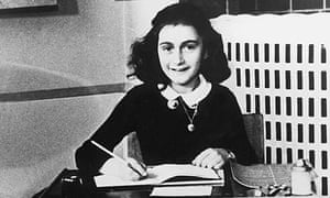Anne Frank photographed at a desk with pen in hand