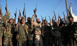 Soldiers loyal to Assad cheer while raising their weapons in the Aleppo countryside.