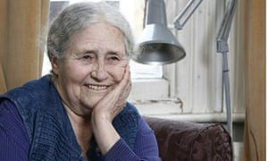 Doris Lessing smiling on a chair in her home