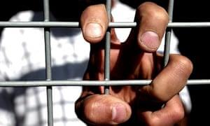 asylum seeker clutching cage grill