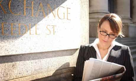 British business woman reading newspaper in the sunshine in the City of London