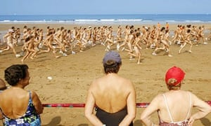 Naked runners start race on beach watched by bathers