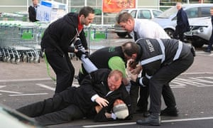 eff6f18b3141c A shopper is restrained on the ground by security staff in the car park of  an