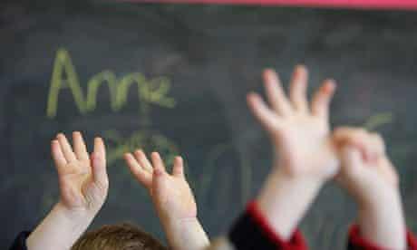Children wave their hands at a nursery school