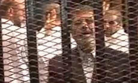 Mohamed Morsi in a cage in a courthouse