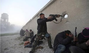 Free Syrian Army fighter fires a rifle through a hole in a wall