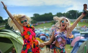 Two young women leap in the air at Glastonbury campsite
