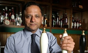 Rooney Anand, chief executive of Greene King, behind a bar at the firm's headquarters