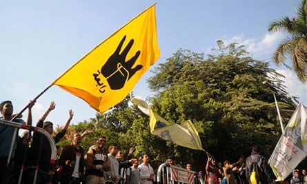 Students of Cairo University, who are supporters of the Morsi, wave a flag bearing the Rabaa sign