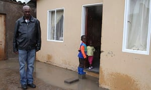Zolile Twebe standing by house with children