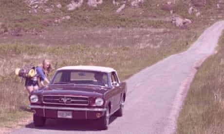 Hiker Meat: American-style car apparently picking up a female hitchhiker on isolated road