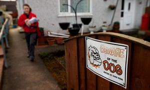 Beware of the dog sign as postman delivers