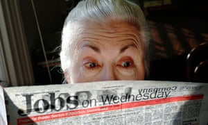 A surprised looking woman pensioner surveys the jobs on offer in her local paper.