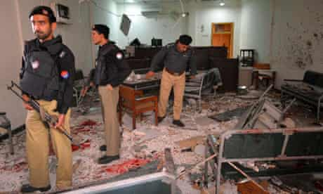 Police examine teh site of the bombing at a court complex, in Peshawar.