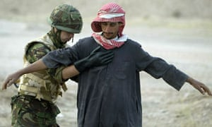 A British soldier stops and searches an Iraqi, at a checkpoint