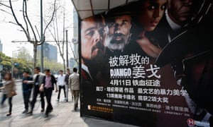 People walk past a poster for Django Unchained outside a cinema in Shanghai