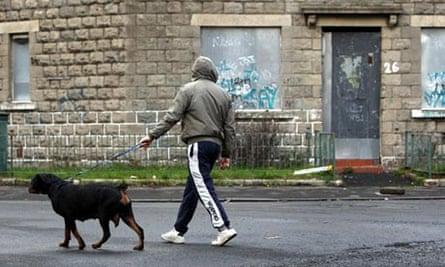 Man in hoodie walking dog in boarded-up street