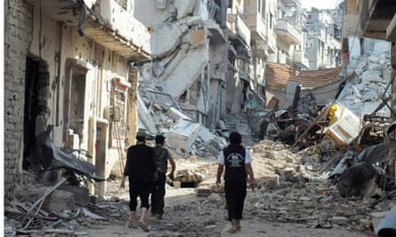 Free Syrian Army fighters walk on rubble of damaged buildings in Juret al-Shayah in Homs