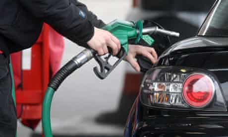 person using pump at petrol station