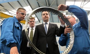 George Osborne looking at a round industrial part at a factury