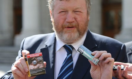 Ireland's health minister, James Reilly, holding plain cigarette packets: 'Smoking places an enormou