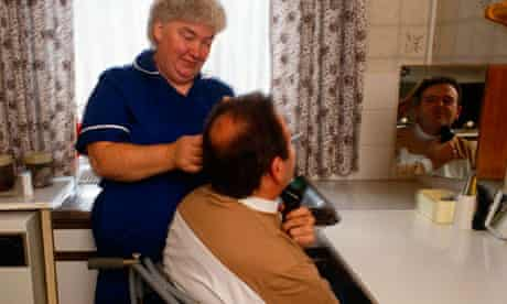 District Nurse helps brush the hair of a disabled man