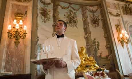 A waiter with a tray in the Ritz hotel restaurant, London