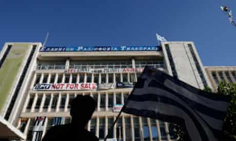 A protester waves a Greek flag outside the ERT HQ