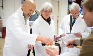 Michael Eavis in white coat helps judge cheese at the Royal Bath and West show