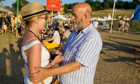 Michael Eavis talks to a smiling female festival-goer.