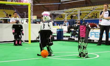 A robot from the University of Bonn dribbles around a Japanese competitor