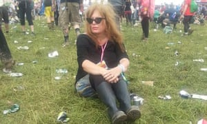 Suzanne Moore sitting amid discarded beer cans in a field at Glastonbury