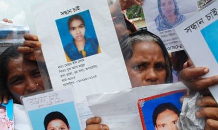 Bereaved mothers hold up pictures of their daughters who died in the factory collapse