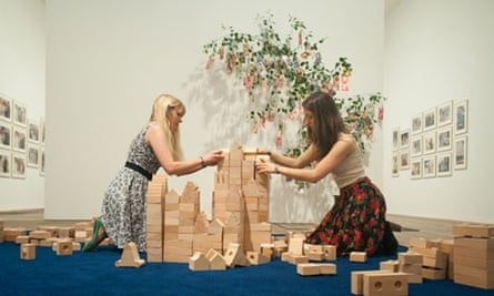 Meschac Gaba's installation: two women creating a tower with building blocks