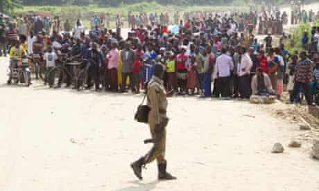 A Ugandan polie officer surveys a crowd of refugees from the Democratic Republic of Congo