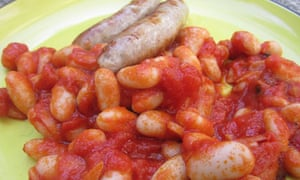 Homemade baked beans with two sausages on a plate