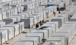 People walk between containers in the refugee camp in Kilis, Turkey