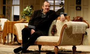 Mel Smith onstage, on sofa