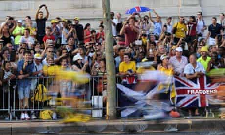 cyclists blurred by motion as they race past crowds
