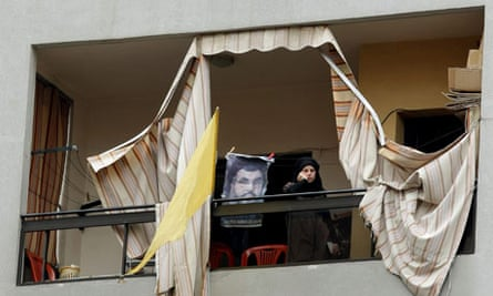 A supporter of Hezbollah stands next to a picture of thegroup's leader Hassan Nasrallah, in Beirut.