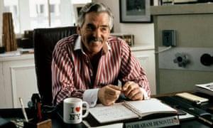Dennis Farina smiling behind a desk in Snatch