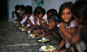 Schoolchildren eat their free midday meal at a primary school in India